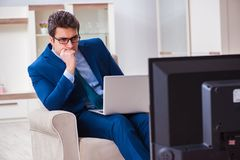 The businesman watching tv in office. Businesman watching tv in office Royalty Free Stock Photo