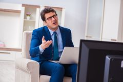 The businesman watching tv in office. Businesman watching tv in office Stock Photography