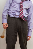 Businesmann alcoholic with empty bottle. Alcoholic wearing suite and tie holding the almost empty bottle Stock Photo