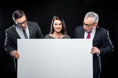 Businespeople holding blank card. Three businespeople holding blank card on black Stock Image