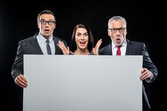 Businespeople holding blank card. Three surprised businespeople holding blank card on black Stock Image