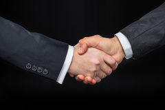 Businespeople shaking hands. Close-up partial view of businespeople shaking hands on black Stock Photos