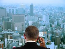 Business. Man discussing to the mobile phone in his office while is looking through the window to the city.Focus on the man, the city aspect is blurred Royalty Free Stock Photography