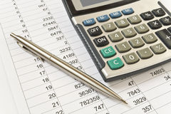 Business. The calculator and the handle on a paper with figures Stock Photography