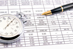 Business. Closeup of an income statement with a pen and stopwatch Royalty Free Stock Photos