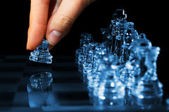 Strategy chess game woman fingers moving pawn. Strategy chess game and player fingers moving pawn with chess pieces made of glass Royalty Free Stock Image