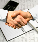 Business. Handshake over paper and pen,blurry computer in the background Royalty Free Stock Image