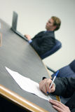 Business. Man types on his laptop while another person signs a contract on a conference table Stock Photos
