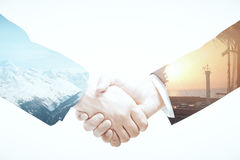 Business abroad. Closeup of businessmen shaking hands on abstract landscape background. Business abroad concept. Double exposure royalty free stock photography