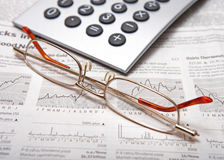 Business accessories. Calculator and glasses on the newspaper with diagram Stock Photos