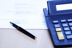 Business accounting. An image of a pen and a calculator on top of a financial statement, can be used for business finance and accounting concept ( shot in blue Stock Image