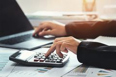 business accounting finance concept. accountant using calculator for calculate  with laptop working in office stock images