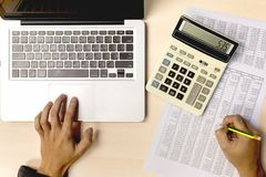 Business accounting using calculator and computer laptop for analyzing investment finance report on desk office royalty free stock photography