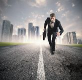 Business in action. With running businessman in a road Stock Images