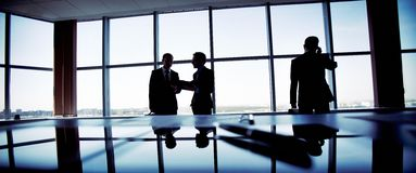 Business activity. Business people spending a usual busy day in office, only silhouettes being recognizable Stock Image
