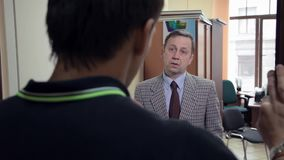 Business adult boss chastises worker man in office cabinet. Business adult caucasian boss in grey checker jacket chastises worker man in office cabinet, over stock footage