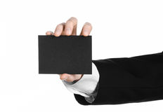 Business and advertising topic: Man in black suit holding a black blank card in hand isolated on white background in studio Stock Image