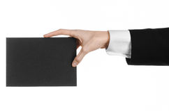 Business and advertising topic: Man in black suit holding a black blank card in hand isolated on white background in studio Stock Photos
