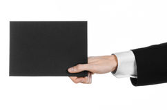 Business and advertising topic: Man in black suit holding a black blank card in hand isolated on white background in studio Royalty Free Stock Photo