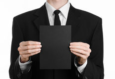 Business and advertising topic: Man in black suit holding a black blank card in hand isolated on white background in studio Royalty Free Stock Photos