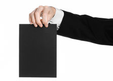 Business and advertising topic: Man in black suit holding a black blank card in hand isolated on white background in studio Royalty Free Stock Image