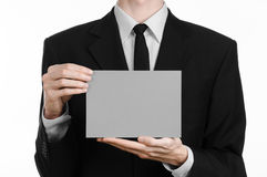 Business and advertising topic: Man in black suit holding a gray blank card in hand isolated on white background in studio Stock Photo