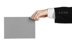 Business and advertising topic: Man in black suit holding a gray blank card in hand isolated on white background in studio Stock Image