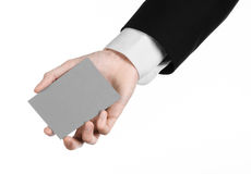Business and advertising topic: Man in black suit holding a gray blank card in hand isolated on white background in studio Stock Photos
