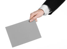Business and advertising topic: Man in black suit holding a gray blank card in hand isolated on white background in studio Royalty Free Stock Images