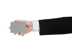 Business and advertising topic: Man in black suit holding a gray blank card in hand isolated on white background in studio Royalty Free Stock Photo