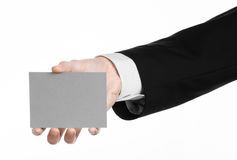 Business and advertising topic: Man in black suit holding a gray blank card in hand isolated on white background in studio Royalty Free Stock Photography