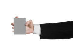 Business and advertising topic: Man in black suit holding a gray blank card in hand isolated on white background in studio Stock Photography