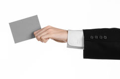 Business and advertising topic: Man in black suit holding a gray blank card in hand isolated on white background in studio Royalty Free Stock Image
