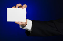 Business and advertising topic: Man in black suit holding a white blank card in his hand on a dark blue background in studio Stock Image