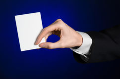 Business and advertising topic: Man in black suit holding a white blank card in his hand on a dark blue background in studio Royalty Free Stock Photo