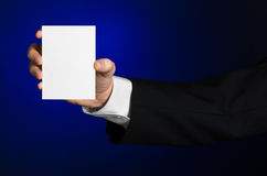 Business and advertising topic: Man in black suit holding a white blank card in his hand on a dark blue background in studio Stock Photography