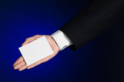 Business and advertising topic: Man in black suit holding a white blank card in his hand on a dark blue background in studio Stock Photos