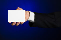 Business and advertising topic: Man in black suit holding a white blank card in his hand on a dark blue background in studio Royalty Free Stock Images