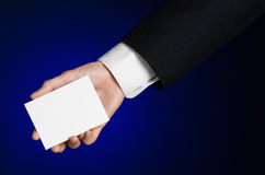 Business and advertising topic: Man in black suit holding a white blank card in his hand on a dark blue background in studio Royalty Free Stock Image