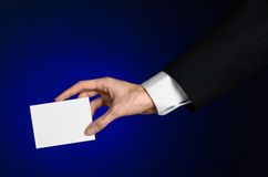 Business and advertising topic: Man in black suit holding a white blank card in his hand on a dark blue background in studio Royalty Free Stock Photography