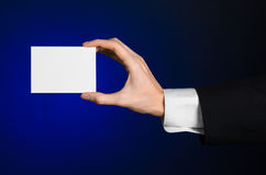 Business and advertising topic: Man in black suit holding a white blank card in his hand on a dark blue background in studio Royalty Free Stock Photos