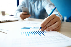 Business adviser analyzing financial figures denoting the progress in the work of company Stock Photo
