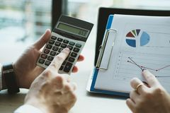 Business adviser working with calculator & financial plan report. Business adviser working with calculator & financial plan report at office. accountant Stock Photography
