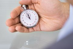 Business advisor holding stopwatch Royalty Free Stock Images