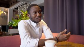 Business African American guy is speaking over cup of coffee with lady, gesticulating with hands actively. Young man is talking to woman, sitting at table in stock video