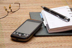 Business Agenda. Phone with paper notebook, pen and glasses, focus on agenda Royalty Free Stock Image