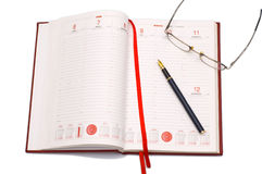Business agenda. Opened business agenda with a pen and eyeglasses Royalty Free Stock Images
