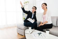 Business agent with client visiting house building. Professional young business agent with client visiting house building and using blueprint document to Royalty Free Stock Images