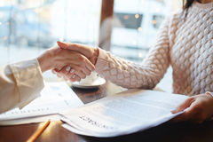 Business Agreement in Cafe. Closeup of two unrecognizable woman partners shaking hands making business agreement over contract and papers during meeting in cafe Stock Photography