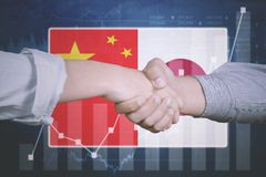 Business agreement with Japan and China flag. Hands of young business team shaking hands for business agreement with Japan and China flag in the background Stock Image